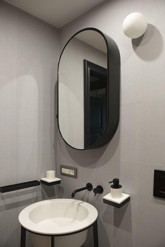 Dettaglio del bagno ospiti con lavabo e specchio contenitore