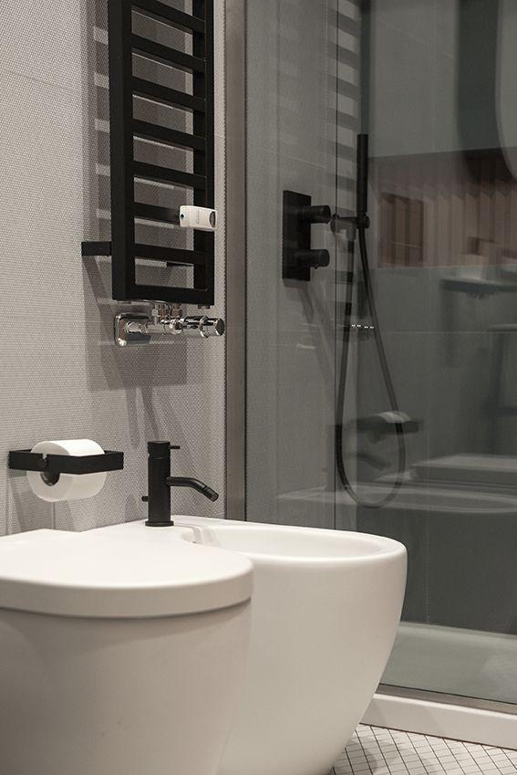 Dettaglio del bagno ospiti con sanitari bianchi, termoarredo e rubinetteria nera