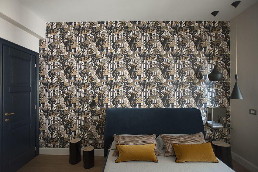 Camera da letto con letto in velluto blu e carta da parati