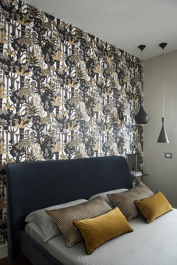 Dettaglio camera da letto con letto in velluto blu e carta da parati
