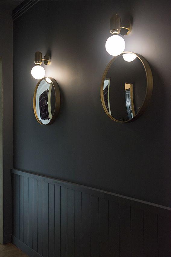 Dettaglio dell'ingresso con boiserie e specchi rotondi