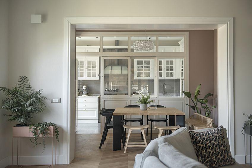 Sala da pranzo con tavolo quadrato e vetrata su cucina