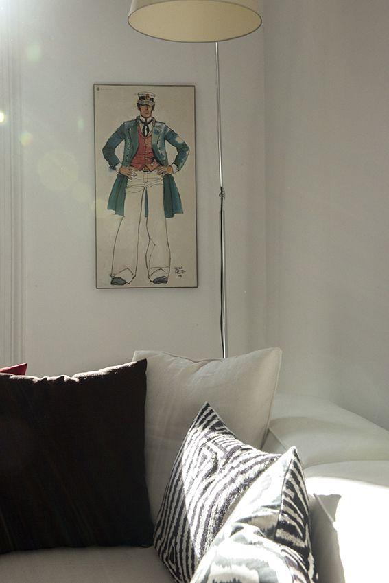 Dettaglio salotto con divano chiaro e lampada Tolomeo di Artemide