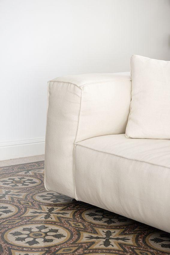 Dettaglio salotto con divano chiaro e pavimento in marmette