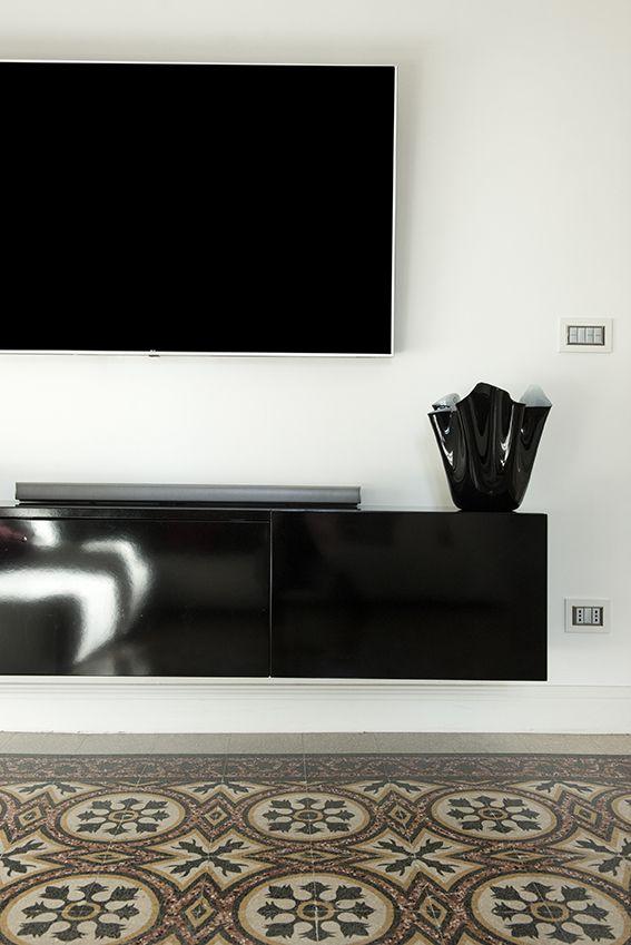 Dettaglio salotto con mobile tv nero sospeso e pavimento in marmette